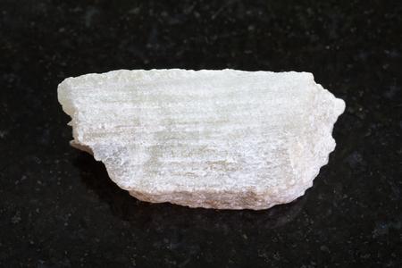 macro shooting of natural mineral rock specimen - raw Talc stone on dark granite background