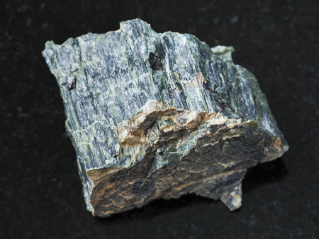 macro shooting of natural mineral rock specimen - raw chrysotile asbestos stone on dark granite background from Saranovskoe mine, Ural Mountains, Russia