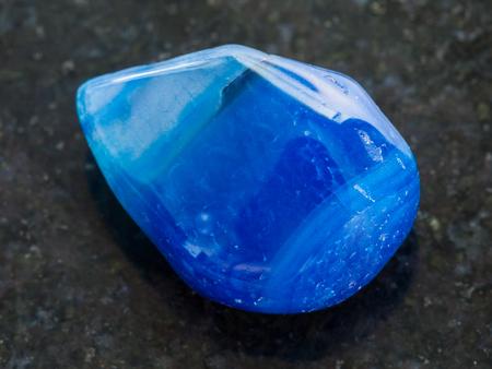 macro shooting of natural mineral rock specimen - polished blue toned agate gemstone on dark granite background