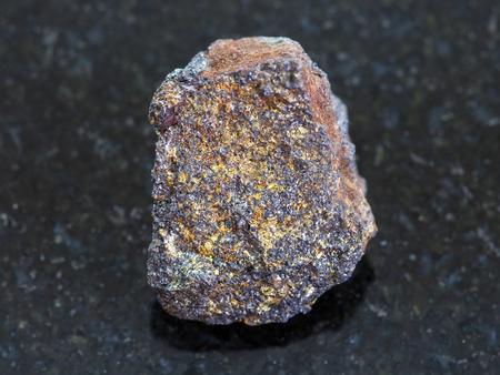 magnetite: macro shooting of natural mineral rock specimen - rough magnetite (iron ore) stone on dark granite background