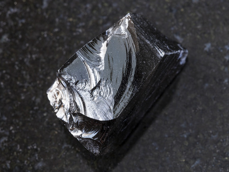 macro shooting of natural mineral rock specimen - piece of raw Obsidian (volcanic glass) stone on dark granite background