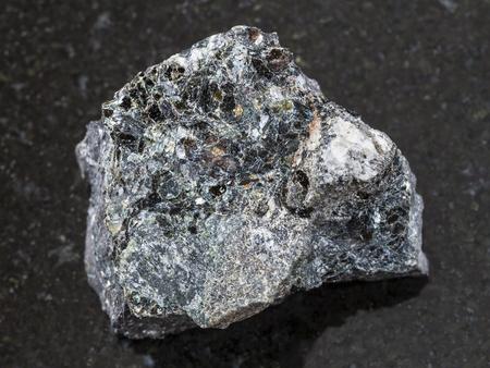 magnetite: macro shooting of natural mineral rock specimen - raw Magnetite ore on dark granite background from Kovdor, Karelia, Russia Stock Photo