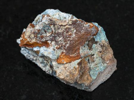 macro shooting of natural mineral rock specimen - raw Scorodite stone on dark granite background from Jezkazgan region, Kazakhstan