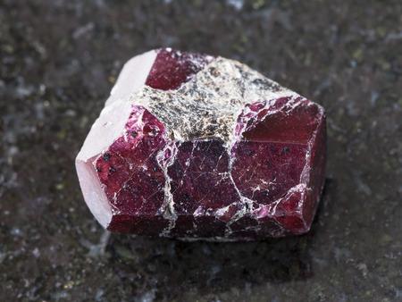 macro shooting of natural mineral rock specimen - rough crystal of red garnet gemstone on dark granite background Foto de archivo