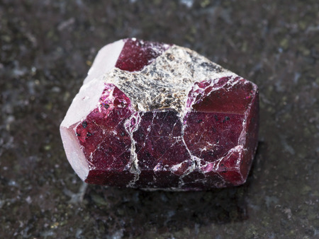 macro shooting of natural mineral rock specimen - rough crystal of red garnet gemstone on dark granite background Stock Photo