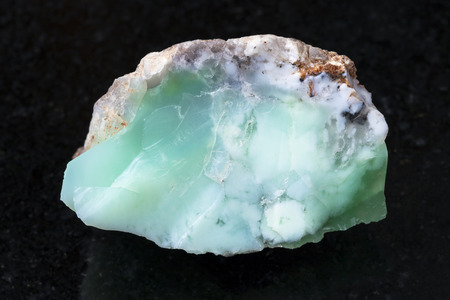 macro shooting of natural mineral rock specimen - rough crystal of Chrysoprase gemstone on dark granite background from Kazakhstan