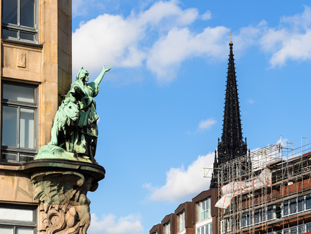 Travel to Germany - outdoor sculpture of old house on Hohe Brucke bridge and steeple of St Nicholas Church (Nikolaikirche) in Hamburg city in september