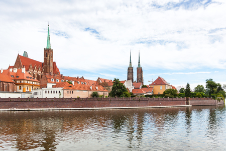 travel to Poland - old Collegiate Church of the Holy Cross and St Bartholomew and towers of Cathedral of St John the Baptist in Ostrow Tumski district in Wroclaw city from Oder River Stock Photo