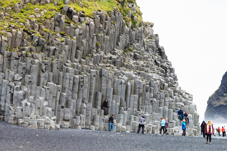 VIK I MYRDAL, ICELAND - SEPTEMBER 9, 2017: tourists near wall of Reynisfjall mount at Reynisfjara black sand lava beach, near Vik I Myrdal village on Atlantic South Coast in Katla Geopark in september Editöryel