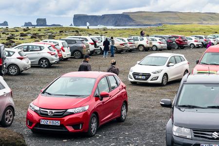 VIK I MYRDAL, ICELAND - SEPTEMBER 9, 2017: people on car parking of Reynisfjara black lava beach in Vik I Myrdal village on Atlantic South Coast in Katla Geopark in Iceland in september