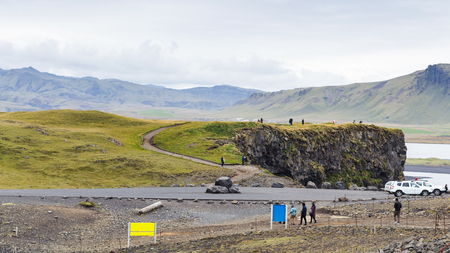 VIK I MYRDAL, ICELAND - SEPTEMBER 9, 2017: tourists on viewpoint near Vik I Myrdal village near Kirkjufjara beach on Atlantic South Coast in Katla Geopark in Iceland in september Stok Fotoğraf - 90557924