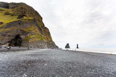 travel to Iceland - tourists near Halsanefshellir cave in Reynisfjall mount on Reynisfjara beach in Iceland, near Vik I Myrdal village on Atlantic South Coast in Katla Geopark in september