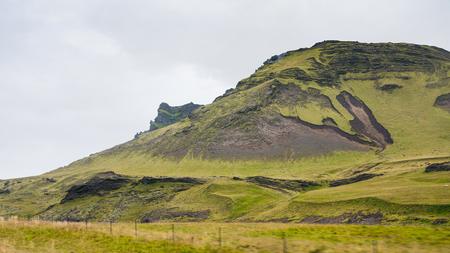 travel to Iceland - green mountain near Vik I Myrdal village on Atlantic South Coast in Katla Geopark in september Stok Fotoğraf - 90742315