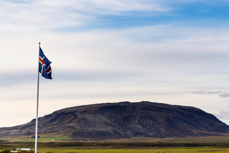 travel to Iceland - icelandic flag and view of hill near Kerid Lake in september evening