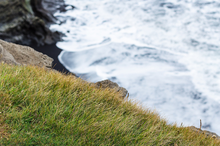 travel to Iceland - green grass on edge of cliff near Vik I Myrdal village on Atlantic South Coast in Katla Geopark in september