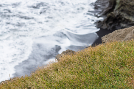 travel to Iceland - green grass on cliff near Vik I Myrdal village on Atlantic South Coast in Katla Geopark in september Stok Fotoğraf - 90742942