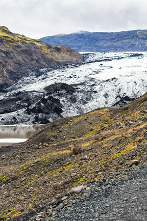 travel to Iceland - volcanic slope and view of Solheimajokull glacier (South glacial tongue of Myrdalsjokull ice cap) in Katla Geopark on Icelandic Atlantic South Coast in september
