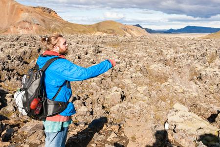 travel to Iceland - man near Laugahraun volcanic lava field in Landmannalaugar area of Fjallabak Nature Reserve in Highlands region of Iceland in september Stock Photo