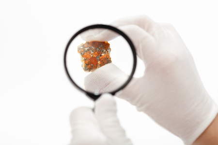 master inspects spessartine garnets with magnifier on white background Stock Photo