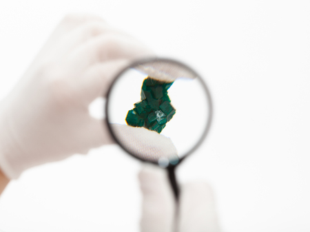 master inspects dioptase crystal with magnifier on white background