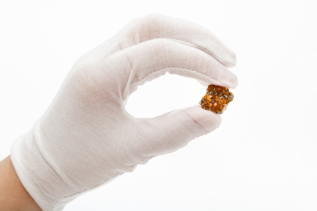 hand in white glove holds spessartine crystals on white background Stock Photo