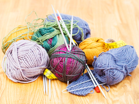 needlework still life - hand knitting instruments and wool yarns on wooden table