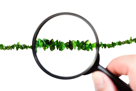 view of chrome diopside necklace through magnifier isolated on white background Stock Photo
