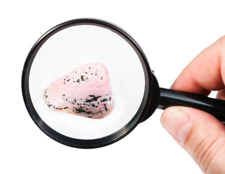view of rhodochrosite gem stone through magnifier isolated on white background