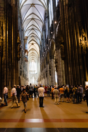 COLOGNE, GERMANY - JUNE 27, 2010: tourists indoor of Cologne Cathedral. The Cathedral is Germanys most visited landmark, attracting an average of 20000 people a day