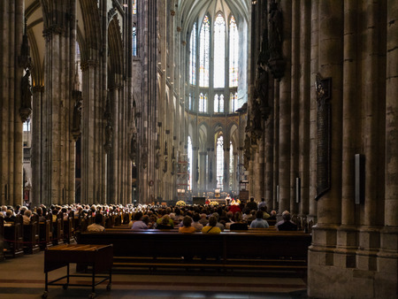 COLOGNE, GERMANY - JUNE 27, 2010: visitors in church service in Cologne Cathedral. The Cathedral is Germanys most visited landmark, attracting an average of 20000 people a day