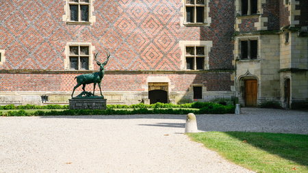 GIEN, FRANCE - JULY 9, 2010: deer statue in court of castle near museum in Chateau de Gien. Chateau was built in the XVth century for Anne of Franc, it was bombed in 1940 and later restored Editoriali