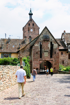 RIQUEWIHR, FRANCE - JULY 11, 2010: tourist walk to gate of Riquewihr city. Riquewihr is commune in Alsace Wine Route region, the town belongs to the association The most beautiful villages of France Editorial