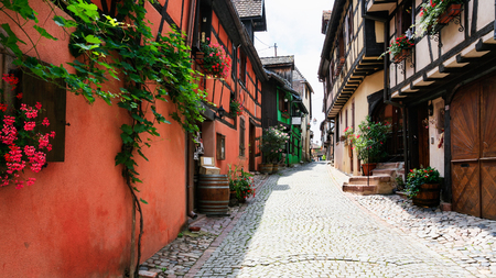 RIQUEWIHR, FRANCE - JULY 11, 2010: street with wine shops in Riquewihr city. Riquewihr is commune in Alsace Wine Route region, the town belongs to the association The most beautiful villages of France