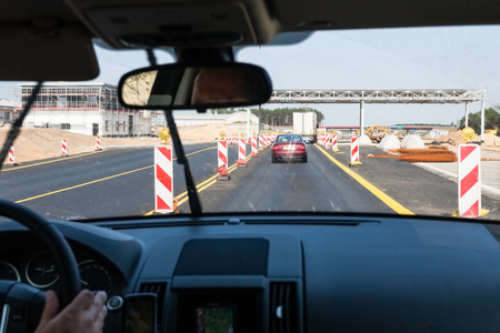 travel to Poland - driving car along repairing area on Autostrada Wolnosci (Motorway of Freedom) A2 (a part of the European route E30 connecting Berlin and Moscow) in summer day Stock Photo