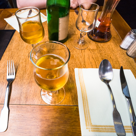 travel to France - local apple cider in wineglass on table in restaurant in Etretat town in Normandy