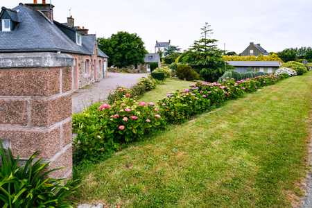 Street with flowerbed in Ploubazlanec commune of Paimpol region in Cotes-d'Armor department of Brittany in summer eveining