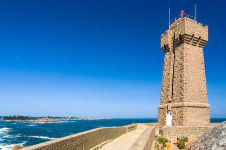 travel to France - edifice of Mean Ruz lighthouse in Ploumanach site on English Channe coast in Perros-Guirec commune on Pink Granite Coast of Cotes-dArmor department of Brittany in sunny day