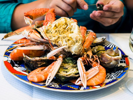 travel to France - visitor eats seafood in local fish restaurant in Treguier town in the Cotes-dArmor department of Brittany