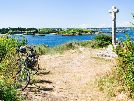 travel to France - tourist bicycle at viewpoint near Celtic cross on Ile-de-Brehat island in Cotes-d'Armor department of Brittany in summer sunny day 免版税图像