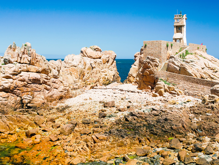 travel to France - Paon Lighthouse (Phare du Paon) on pink granite coast of Ile-de-Brehat island in Cotes-dArmor department of Brittany in summer sunny day Stock Photo