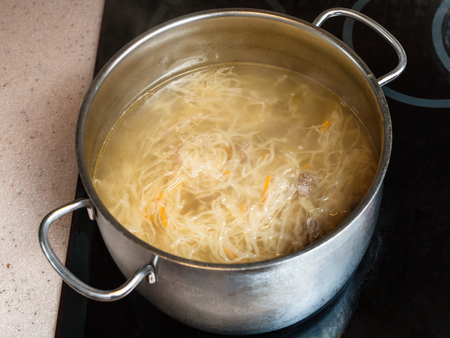 cooking soup - cabbage soup with stewed sauerkraut in stewpan on ceramic cooker