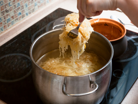 cooking soup - the cook moves stewed sauerkraut from ceramic pot into saucepan with meat broth