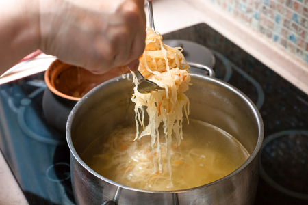 cooking soup - the cook transfer stewed sauerkraut from ceramic pot into saucepan with meat broth
