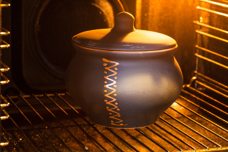 cooking soup - closed ceramic pot with stewed cabbage in illuminated electric oven