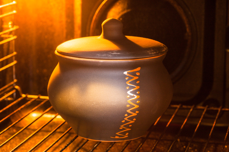 cooking soup - closed ceramic pot with stewed vegetables in hot electric oven