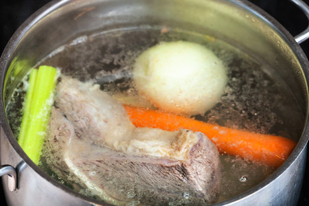 cooking soup - boiling beef broth in steel stewpan close up Stock Photo