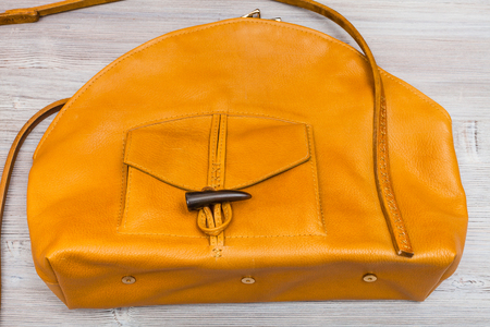 handmade yellow leather bag with pocket on wooden table Stock Photo
