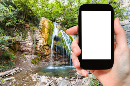 travel concept - tourist photographs Ulu-Uzen river with Djur-djur waterfall in Haphal Gorge of Habhal Hydrological Reserve natural park in Crimea on smartphone with cut out screen for advertising