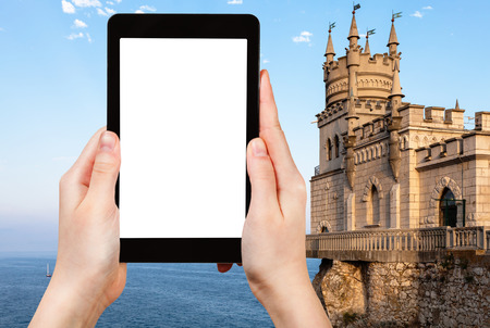 travel concept - tourist photographs Swallow Nest Castle over Black Sea in Gaspra District on Crimean Southern Coast in september evening on tablet with cut out screen for advertising logo Stock Photo