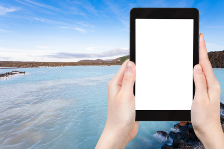 travel concept - tourist photographs Blue Lagoon Geothermal lake in Grindavik lava field outside spa resort in Iceland in autumn evening on tablet with cut out screen for advertising logo view of 스톡 콘텐츠